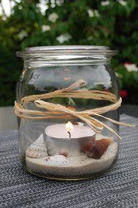 Aus Sand und Muscheln können Kinder ein Windlicht basteln.