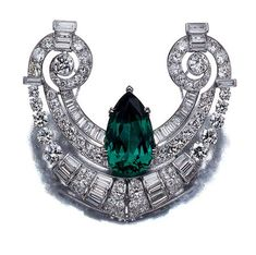 Simulated Emerald and Diamond Brooch   Platinum,the stylized openwork scroll motif centering one pear-shaped simulated emerald, accented by 86 old European and single-cut and 42 baguette diamonds, approximately 10.75 cts., circa 1930