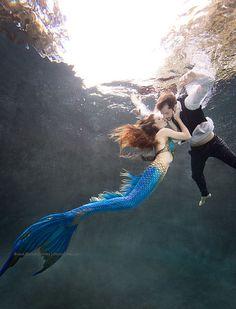 Mermaid kissing a sailor at the water's surface