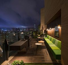 This modern residential building in Hong Kong has a barbeque area with built-in bench seating and wood accent walls.