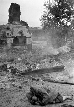 A Russian woman tries to shelter her infant amidst the ruins while Axis forces shell of the small village of Krasnaya Sloboda during Operation Barbarossa, the Axis invasion of the Soviet Union. Krasnaya Sloboda, Bryansk Oblast, Russia, Soviet Union. 30 August 1941. Image taken by Anatoly Garanin.