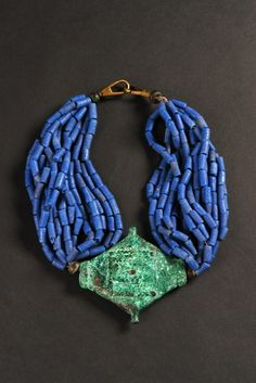 Mali, made of several strings dulled blue glass beads, a rhomb-shaped pendant made from metal decorated with geometric ornaments