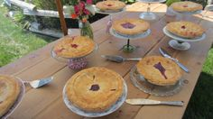 Ollieberry and Strawberry Rubarb pies arranged on a farm table on varying height antique platters