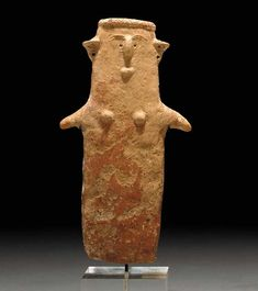 A CYPRIOT TERRACOTTA PLANK-SHAPED IDOL   Middle Cypriot, Circa 1900-1600 B.C.   Of red polished ware, the solid figure with small projecting arms, applied rounded breasts, and projecting, perforated ears, the face with a small chin or mouth, a ridged nose, arching brows and indented eyes, wearing a turban with incised zig-zag  9½ in. (24.1 cm) high