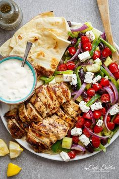 Greek Lemon Garlic Chicken Salad with an incredible dressing that doubles as a marinade! Complete with Tzatziki and homemade flatbreads, it's a winner!
