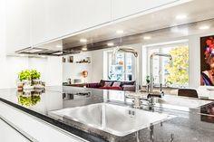 Spegel som stänkskydd ger extra ljus i köket. Riksbyggens Brf Landmärket, Sundbyberg