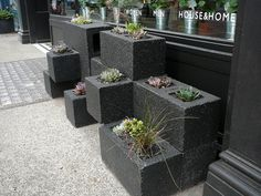 Macetas hechas con bloques de cemento afuera de un negocio