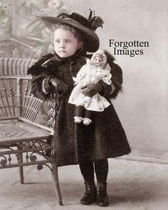 Victorian era girl holding her doll. 1890s.