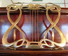A 1910, Allison exhibition upright piano with a polished, mahogany with elaborate bronze mountings. Art nouveau style music stand.