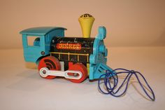 """1960s Plastic and wood pull toy in bright blue plastic with red wooden wheels. Original pull string. Cheerful toy or decoration for a nursery or playroom. Measures: 6 1/2"""" x 3 1/4"""" x 3 1/2"""""""