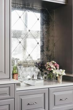 Gray kitchen bar features an antiqued mirror diamond pattern backsplash tiles positioned above a white quartz countertop framed by gray shaker cabinets fit with satin nickel hardware.