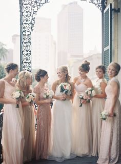 Mismatched bridesmaid dresses in shades of pink and neutral.