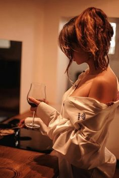 Woman featuring a very sexy shoulder and breast, holding a glass of wine.