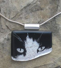 Great piece - a Dichroic Fused Glass Cat Necklace.... Dichroism has two distinct meanings in optics. A dichroic material is either one which causes visible light to be split up into distinct beams of different wavelengths (colours), or one in which light rays having different polarizations are absorbed by differing amounts. Glass artists  use fusing glass scrap packs to layer dichroic glass to make multi layered fused glass pieces. Would love to see this process.