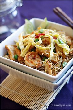 """Mee Siam (Spicy Rice Vermicelli) recipe - Mee Siam or """"Siamese noodles"""" is basically spicy fried rice vermicelli with various toppings such as shrimp, chicken, fried firm tofu, and shredded omelet. Mee Siam is usually served with a piece of kalamansi lime (the juice gives an extra tangy kick to the noodles) and a dollop of sambal on the side. #malaysian #noodles"""