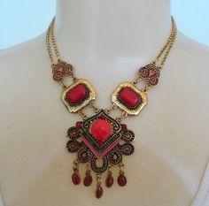 Maxi colar feito em placa de metal dourada com detalhes em resina. R$ 14,00