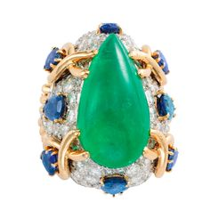 David Webb: A Multi-gem and Diamond Ring, centering upon a pear-shaped cabochon emerald, weighing an estimated 11.00 carats, mounted above a dome set with an estimated total weight of 5.50 carats of round brilliant-cut white diamonds, the dome enhanced with eight pear-cut blue sapphires with an estimated total weight of 7.20 carats, four of the sapphires enhanced with yellow gold wire surrounds, set in 18k gold and platinum, signed David Webb, circa 1960.