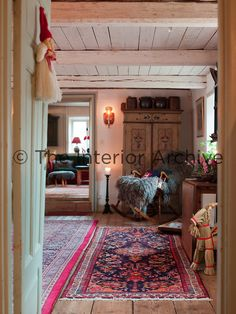A view through a doorway into the dining room, where a welcome rocking chair awaits you Swedish Farmhouse, Swedish House, Scandinavian Living, Entry Hall, Ceiling Beams, Doorway, Cozy House, Rocking Chair, Cottage Style