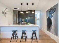 """Em tons de cinza e branco, a cozinha americana clássica com sua bancada para refeições e três pendentes cônicos sobre a mesma. A dupla já é uma """"equação resolvida"""" para as casas: inevitavelmente, ao se criar uma cozinha americana - ou seja, uma..."""