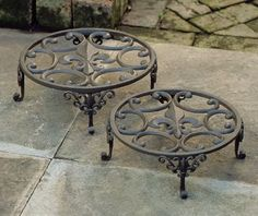 by charlestongardens.com  Fleur De Lis Plant Stands (Set of Two $68.00    These plant stands are great looking and you can never have enough of them. Stands like this keep your pots up off the ground, giving them room to drain properly outdoors, and keeping them from ruining your favorite floors indoors. It's actually quite a shame that the fleur de lis will be covered during the warm season.