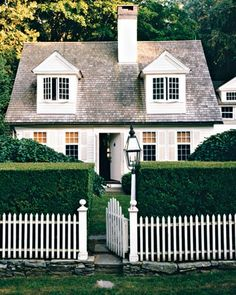 White cottage with tall boxwood hedges, fence, lantern - Martha Stewart