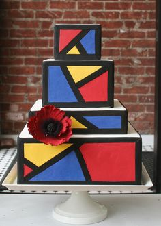 """Inspired by Roy LIchtenstein's 1962 """"The Kiss II"""", this cake was designed in a color blocking motif. Includes handmade red sugar poppy ."""