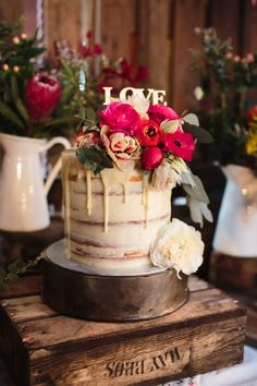 single tiered, semi-naked wedding cake dressed in fresh pink flowers
