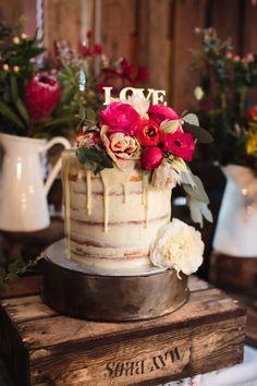 single tiered, semi-naked wedding cake dressed in fresh pink flowers