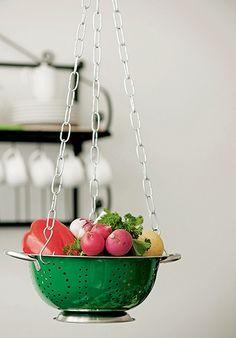 Com um escorredor e correntes para vasos, você monta em um estante um suporte para deixar legumes e outros ingredientes à mão na hora de preparar as receitas. O acessório também pode ser usado como fruteira suspensa. Produção de Ellen Annora