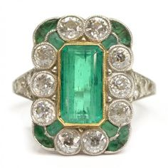 Ladies Art Deco gemset platinum estate ring having 18kt gold bezel, the rectangular frame set with: (1) central emerald, approx 1.42 cts total weight; (12) caliber-cut emerald; (18) old European cut diamonds, approx 1.43 cts total weight.