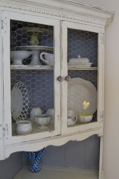 Distressed, Chalkpainted Corner Hutch. I LOVE this chicken wire accent on the glass!
