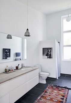 Modern and nordic bathroom with bright furniture and an ethnic carpet.