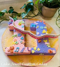 Adorable pink and purple eleven cake decorated with flowers, dots, butterflies and music notes