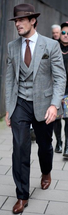 A grey with brown color combo is a challenge, but the colors looks great together.  I love the brown fedora and brown shoes.  However, this look would be improved if the coat and pants had a slimmer cut (or if he had a camelhair overcoat)