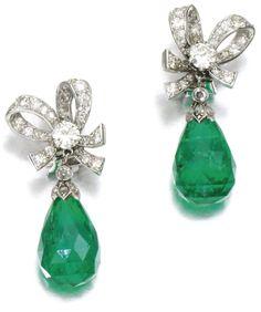 Diamond and emerald earrings with bow-shaped diamond surmounts suspending emerald drops. Via Sotheby's.