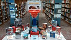 """May Book Display: """"Make a SLAM DUNK! with National Physical Fitness and Sports Month.""""  I borrowed our daughter's Little Tykes basketball hoop and a few pieces of sports equipment from home, then added a variety of nonfiction and biographical sports titles, as well as two fitness DVDs."""