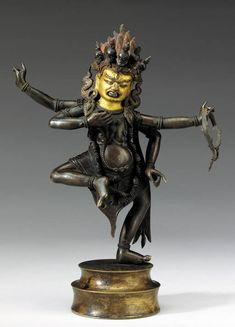 A Bronze Figure of a Dharmapala   Tibet, 17th/18th Century   The four-armed deity dancing with a ferocious expression with flaming hair and a skull tiara, wearing a tiger-skin dhoti and a garland of severed heads  8 1/8 in. (20.5 cm.) high
