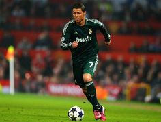 Real Madrid's Portuguese forward Cristiano Ronaldo runs with the ball during the UEFA Champions League round of 16 second leg football match between Manchester United and Real Madrid at Old Trafford in Manchester, northwest England on March 5, 2013.
