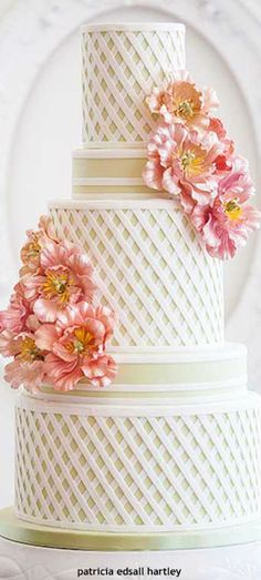 Three tiers of lattice-work white wedding cake with coral-pink flowers.