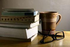 eyeglasses, books and coffee mug - photo of a pair of eyeglasses, old books and a coffee mug on a wooden table