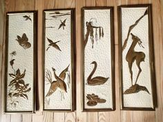 Set of 4 embossed brass Danish Modern Mid Century wall plaques. Stylized deer, swans, birds and flower, textured background is enameled white and set off the embossed figures on each piece.