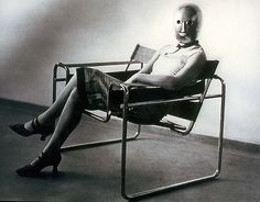 This startling 1926 photograph shows the B3 club chair, the Wassili chair by Marcel Breuer, named after Bauhaus professor Wassili Kandinsky. Both Breuer and Kandinsky were Bauhaus teachers. The chair was a product of functionalist thinking about design, inspired by Breuer's bicycle.    The photograph was shot by Bauhaus student Erich Consemüller and shows a woman, either Bauhaus weaving graduate Lis Beyer or Ise Gropius, wife of Director Walter Gropius.
