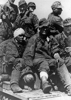 1943, Union Soviétique, Koursk, Des Waffen-SS assis sur le pont d'un Panzer. Celui au premier rang est blessé  