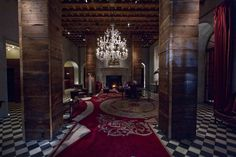 The Lobby at the Gramercy Hotel, New York has black and white checkered floors, red carpeting, wooden columns, exposed ceiling structure, large stone fireplace, arched openings, red drapes, and hanging chandelier.