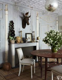 A 1900 handcarved wood deer hangs over the dining area mantel decorated with objects #gustavian