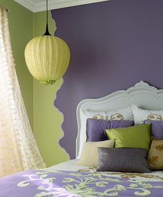 The wall pattern echos the shape of the headboard, .....complementary colors of lime green and hazy purple are pleasing to the eye. my paint my bedroom these or similar colors next time i get the mood to paint