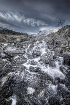 A cold winter morning, looking upstream on the Afon Idwal, or Idwal river, towards Cwm Idwal and a snow covered Clogwyn y Geifr or Cliff of Goats and The Devil' Kitchen in the heart of Snowdonia in North Wales.  A lone, wind-ravaged tree clings to it's foothold in a rock crevice on the right hand bank of the river while whispy white clouds brush the mountain tops.