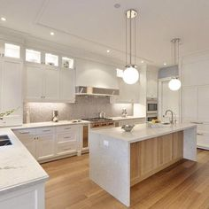 This kitchen features a beautiful Caesarstone countertop in Bianco Drift #6131, very low maintenance to keep them looking brand new. The white cabinets compliment the warm wood floors and island.
