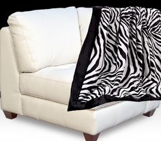 "Zebra Essence Black Border Throw  Elegant Zebra Throw !  Faux Fur Zebra Print Throw, with a Black Faux Fur Border.  Reversible, with solid Black Faux Fur on the reverse side.  This Zebra throw is an elegant addition to any sofa, chair, or bed.  Not to mention the snuggle warmth, and comfort. The Zebra print design is a white background with black zebra stripes that include the main pattern for a realistic look.  Exotic Zebra Animal Essence . Approximately 50""x60""   $85.99 SALE $76.00"