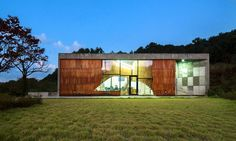 """For the artist, they created what they call Skinspace: a cast-concrete building with a facade that is both skinlike and spatial, or three-dimensional. Clad in plywood """"scales,"""" it rolls inward behind a glassy entry zone, like sequins on a curved surface. Where the facade bends, it becomes a slatted sunscreen, opening the interior to views of mountains, terraced farms and rice paddies."""